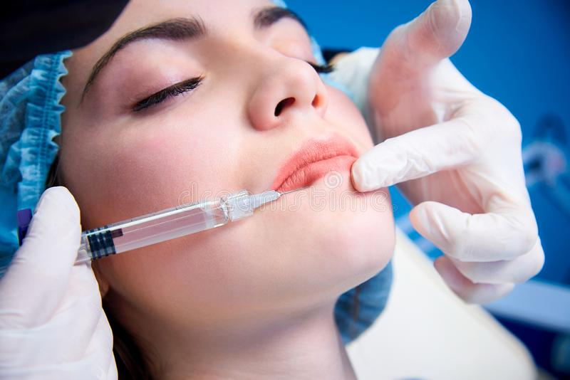 Cosmetic procedures. Beautiful young woman gets injection in lips.Beauty injections and cosmetology.Plastic and aesthetic surgery stock photos