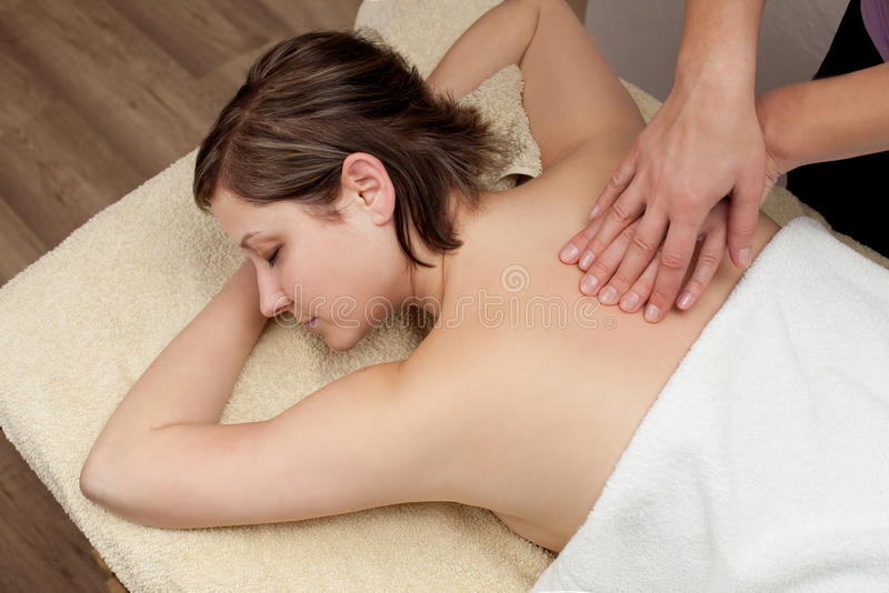 Beautiful young woman getting a back massage royalty free stock image