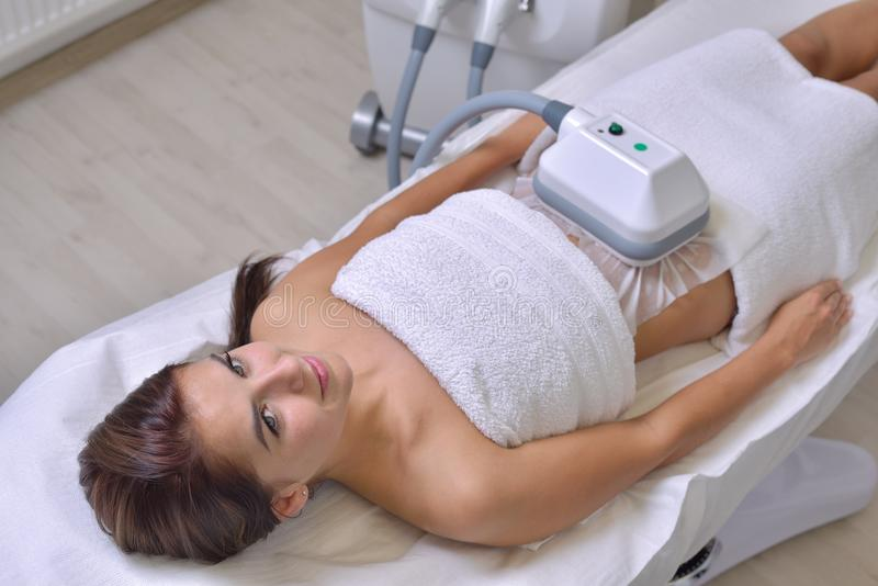 Beautiful young woman getting cryolipolyse treatment in cosmetic. Cabinet stock photo
