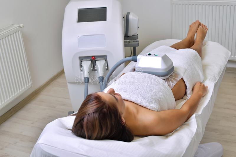 Beautiful young woman getting cryolipolyse treatment in cosmetic. Cabinet royalty free stock photography