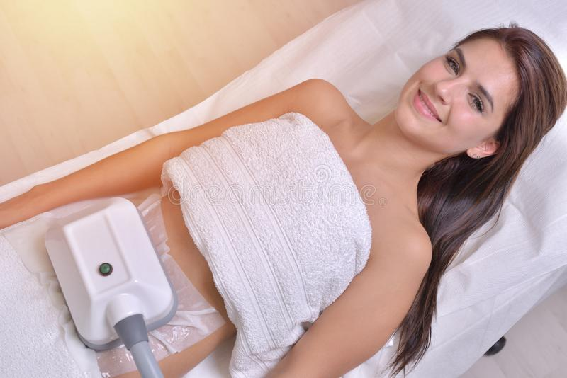 Beautiful young woman getting cryolipolyse treatment in cosmetic cabinet.  stock image