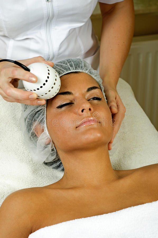 Beautiful young woman getting face massage. royalty free stock image