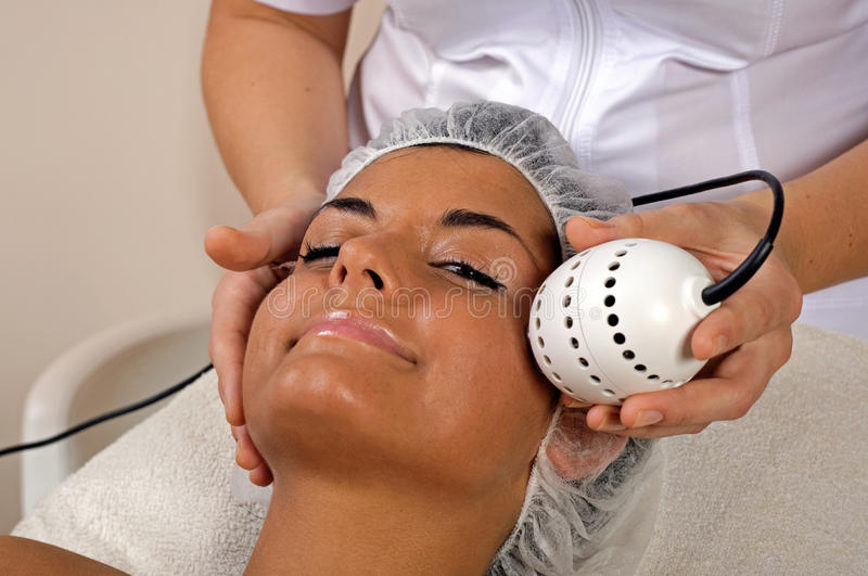 Beautiful young woman getting face massage. stock photo