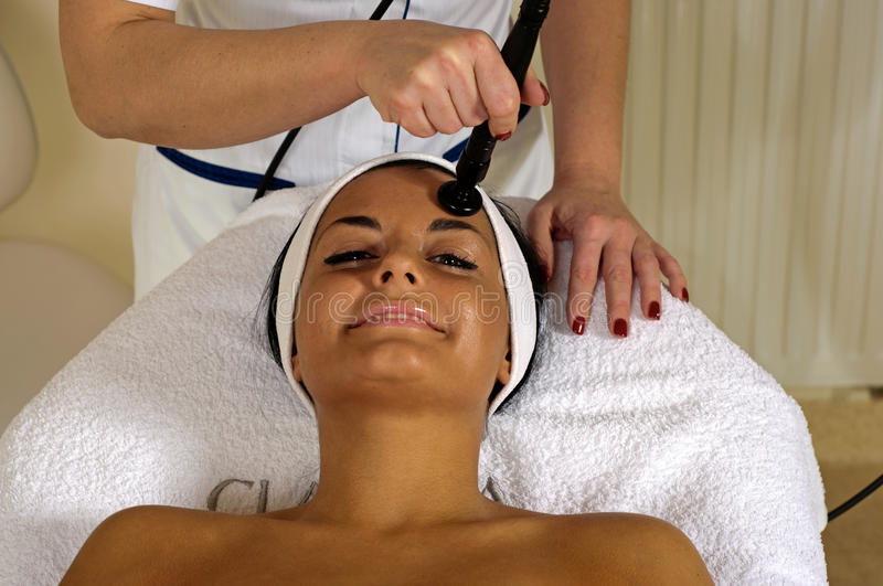 Beautiful young woman getting face massage. royalty free stock photo