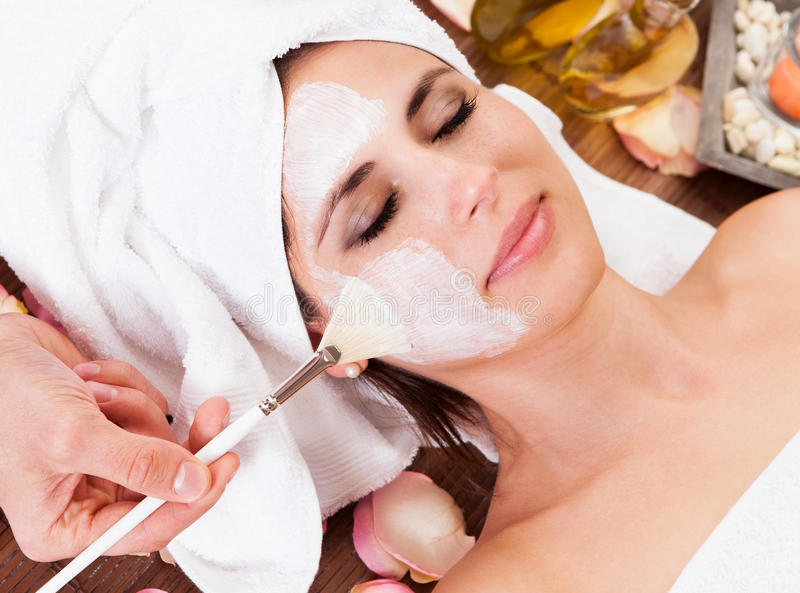 Beautiful young woman getting facial mask. At spa studio stock images