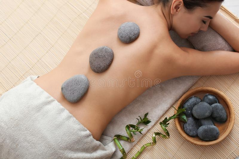 Beautiful young woman getting hot stone massage royalty free stock photo
