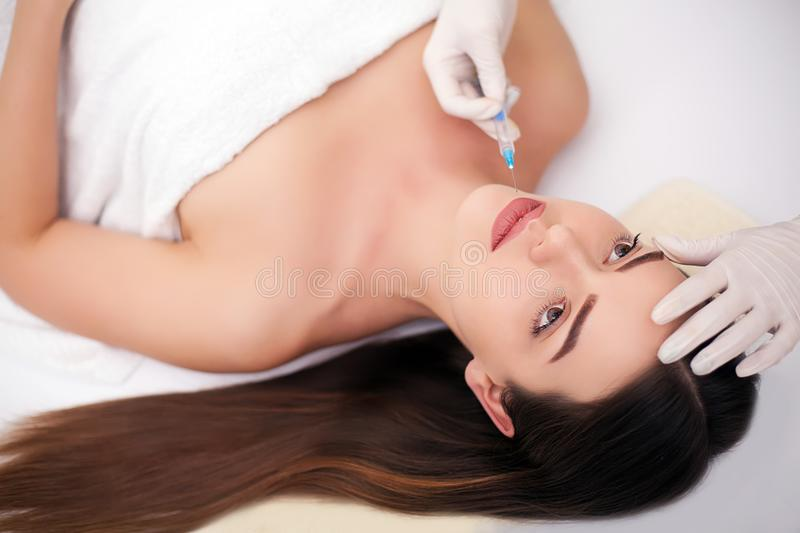Beautiful young woman is getting injection at clinic. She is sitting and smiling. The doctor is holding syringe near her eyebrows royalty free stock images