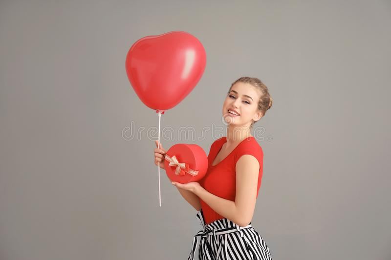 Beautiful young woman with gift box and heart-shaped balloon on color background royalty free stock photos