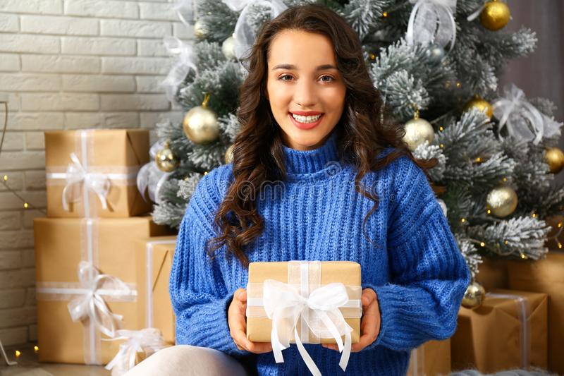 Beautiful young woman with gift box near Christmas tree stock image