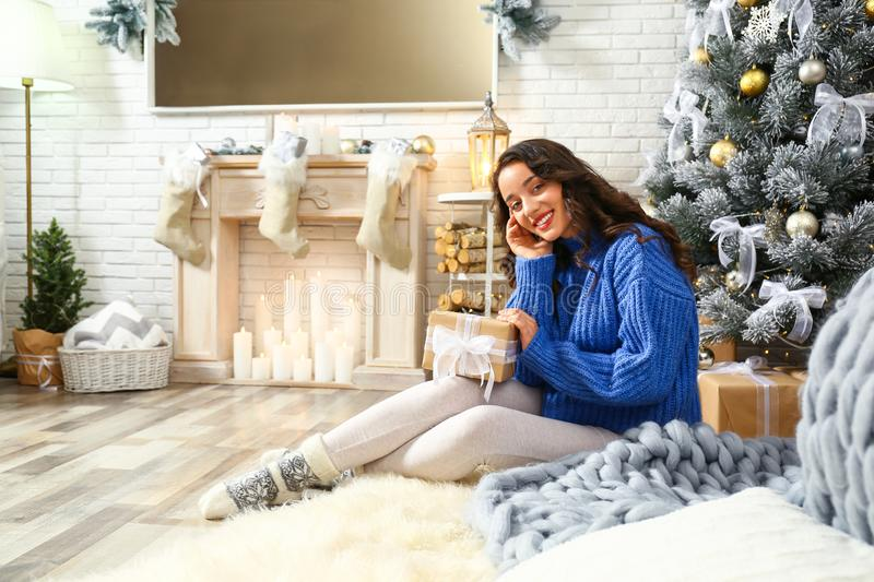 Beautiful young woman with gift near Christmas tree at home royalty free stock images