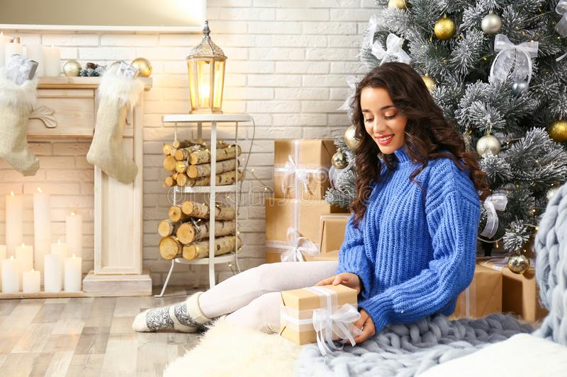 Beautiful young woman with gift box near Christmas tree stock photos