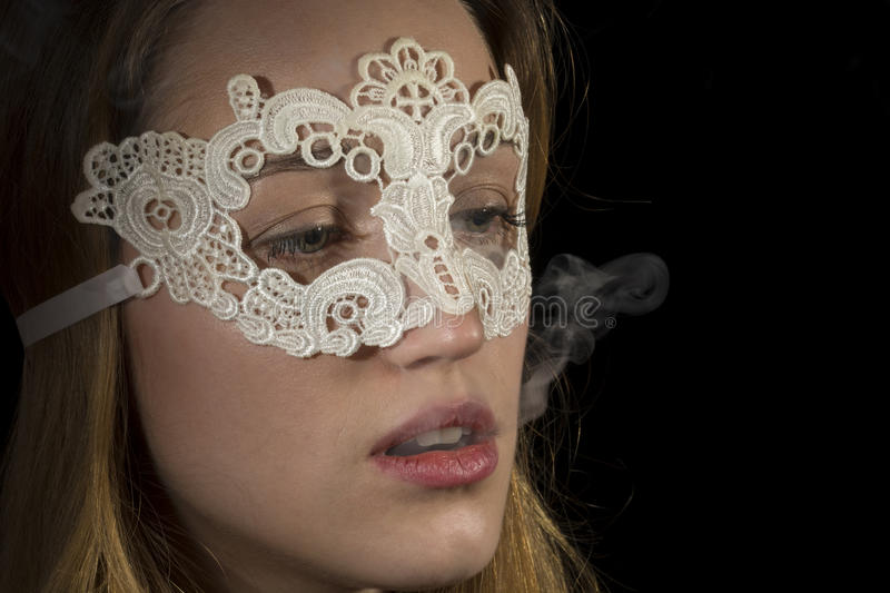 Beautiful young woman. Young girl with lace mask and smoking stock image