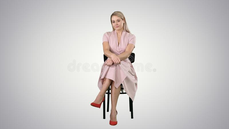 Beautiful young woman, girl, model blonde with long hair sitting on a chair and looking to camera on gradient background stock photos