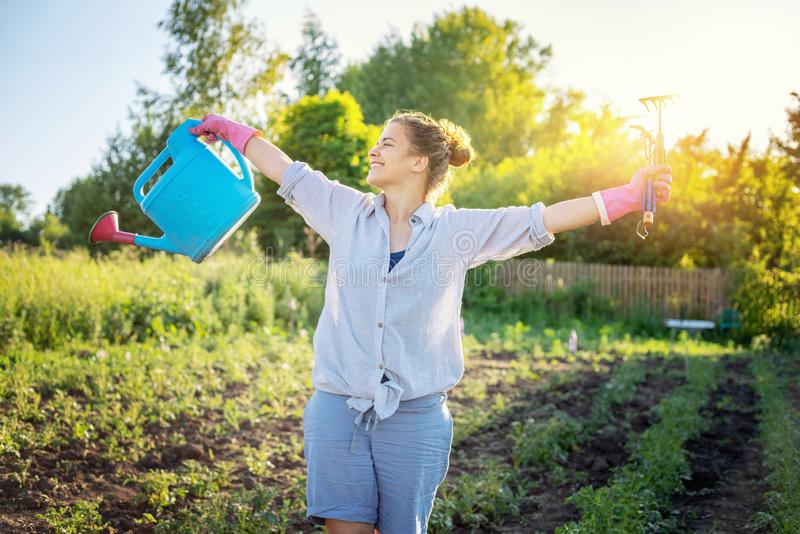 Beautiful young woman girl with a watering can and a rake in her hands, work in the garden and eco-friendly lifestyle royalty free stock photography