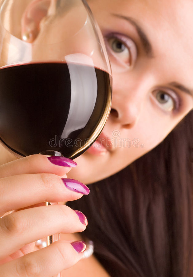 Beautiful young woman with glass of red wine. (Glass in focus royalty free stock photo