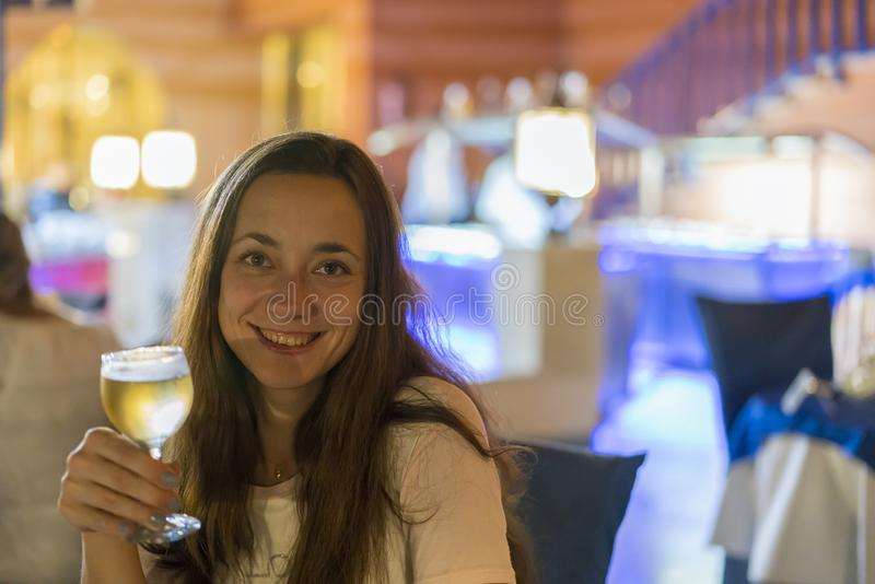 Beautiful young woman with a glass of wine on a blurred background royalty free stock images