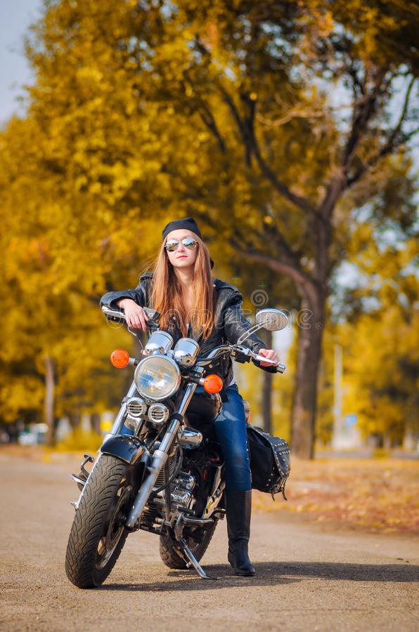 Beautiful young woman in a glasses on a motorcycle stock photo