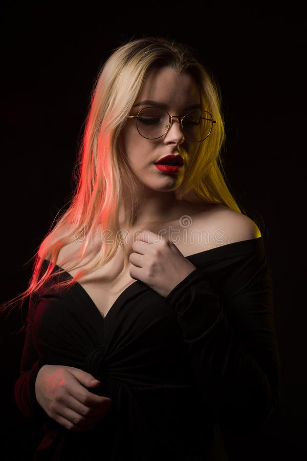 Beautiful blonde woman in glasses wearing blouse with naked shoulders, posing with red and yellow light. Beautiful young woman in glasses wearing blouse with stock photos