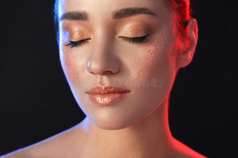 Beautiful young  with glitter makeup on black background royalty free stock photo