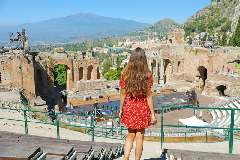 Beautiful young woman goes down the stairs in the ruins of the ancient Greek theater of Taormina with the Etna volcano on the royalty free stock photos
