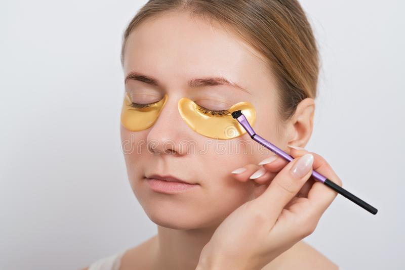 Beautiful young woman with gold hydrogel patches under eyes, iso stock photography