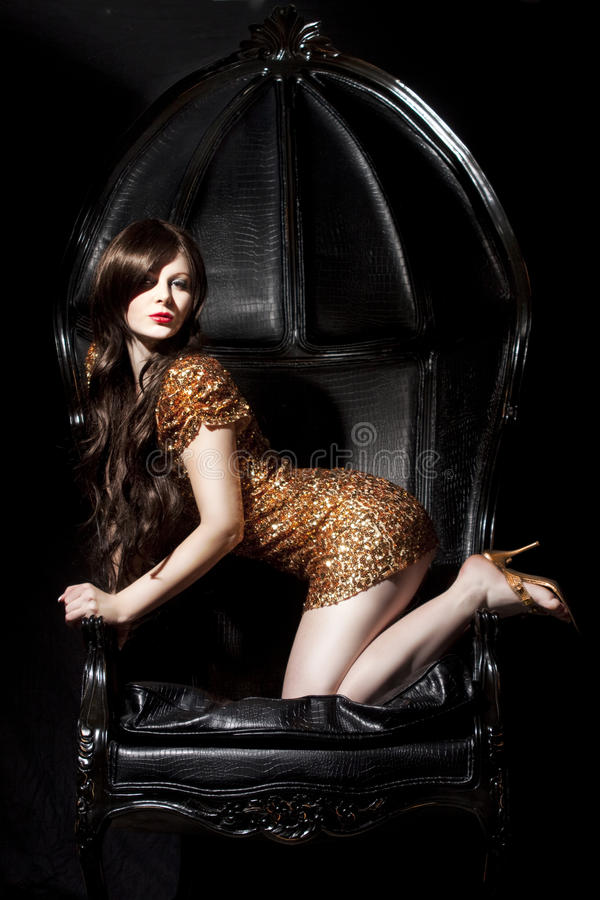 Beautiful young woman. With golden dress in a baroque chair stock images
