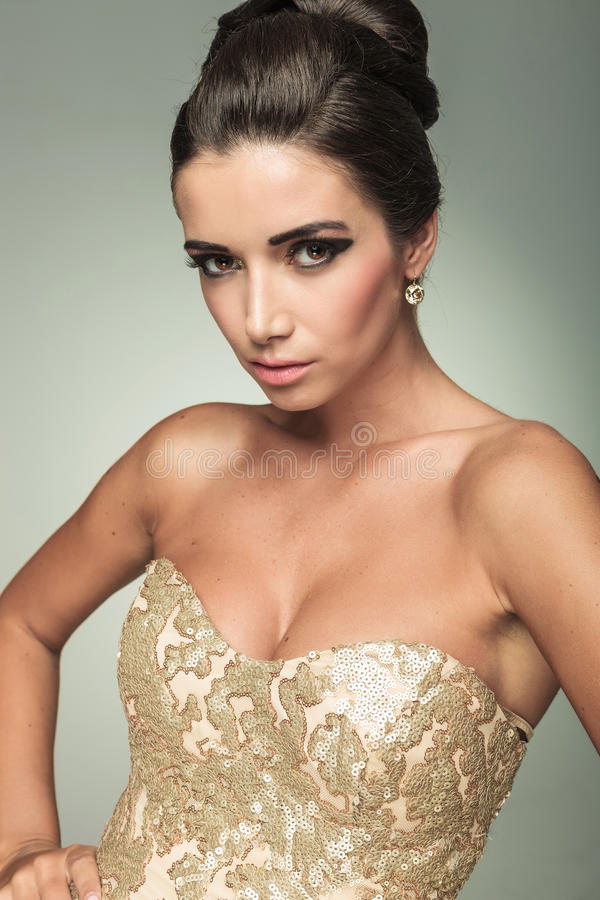 Beautiful young woman in golden dress stock image