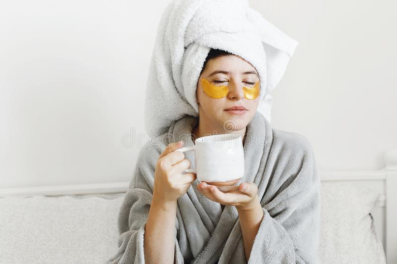 Beautiful young woman with golden eye patches and in bathrobe holding cup of coffee and lying in bed, enjoying morning routine. royalty free stock photo