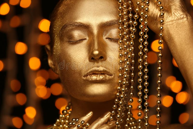 Beautiful young woman with golden paint on her body and beads against defocused lights, closeup stock image