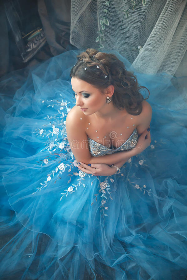 Beautiful young woman in gorgeous blue long dress like Cinderella with perfect make-up and hair style. In interior stock photos