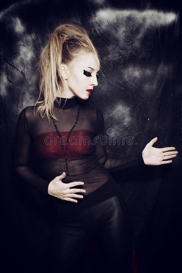 Beautiful young woman with gothic makeup. On black background royalty free stock photography