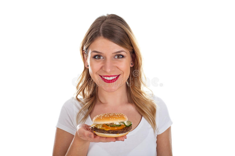 Beautiful young woman with hamburger. Picture of a smiling young woman holding a tasty hamburger royalty free stock images