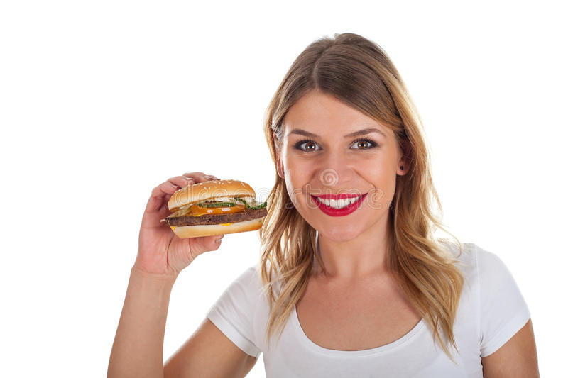 Beautiful young woman with hamburger. Picture of a smiling young woman holding a tasty hamburger royalty free stock photos