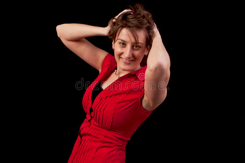 Beautiful young woman with hands in hair isolated on black background royalty free stock images