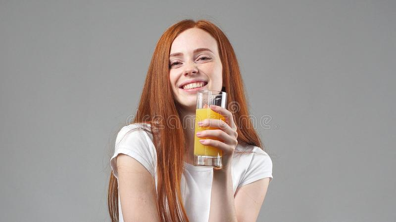 Beautiful young woman happy and drinking orange juice. young woman holding glass of orange juice stock photography