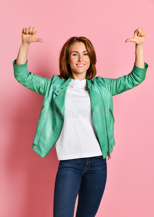 Beautiful young woman happy and excited expressing winning gesture. Successful and celebrating victory, triumphant. Pink background royalty free stock image