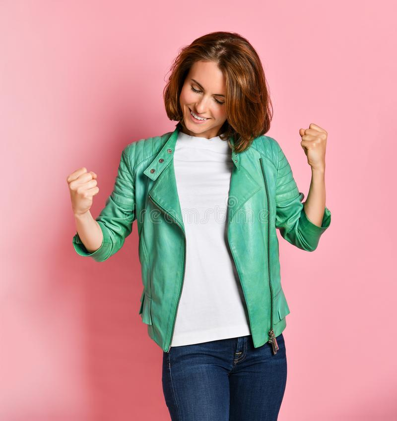 Beautiful young woman happy and excited expressing winning gesture. Successful and celebrating victory, triumphant. Pink background royalty free stock images