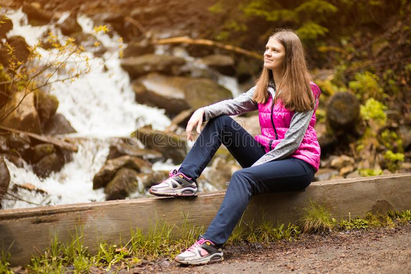 Beautiful young woman happy near forest waterfall stock images