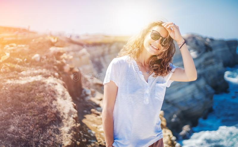 Beautiful young woman with a happy smile in a white T-shirt on the ocean in Portugal, travel and relax royalty free stock photography