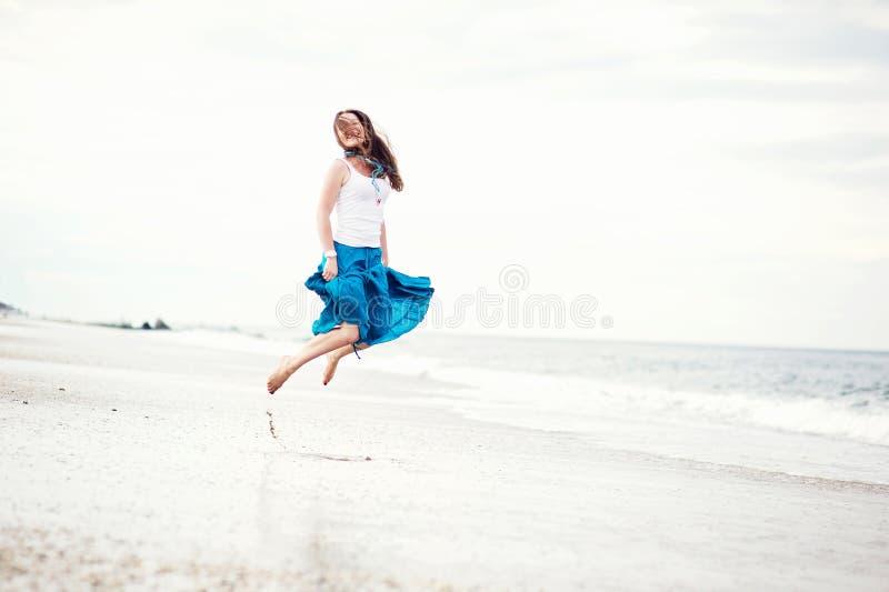 Beautiful young woman has fun on the ocean shore