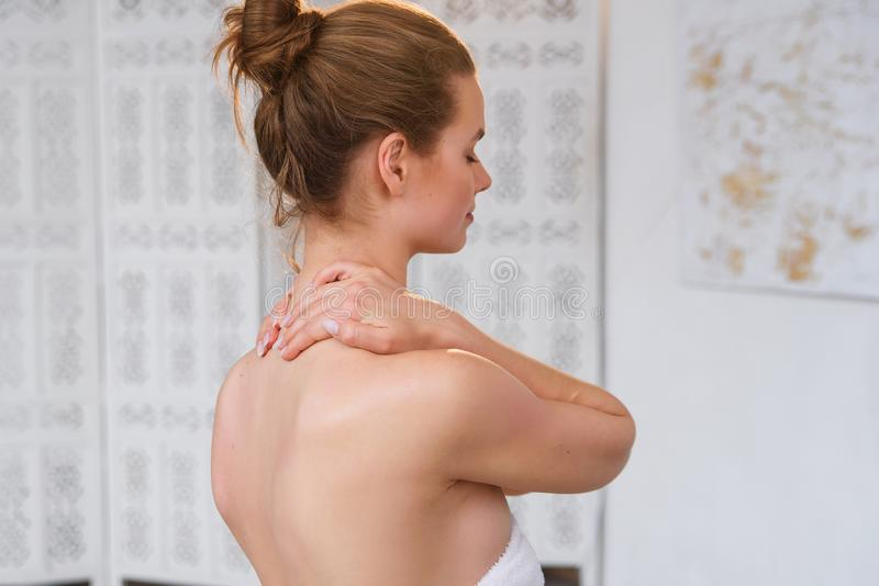 Beautiful young woman has neck pain. Female suffering from painful feeling in muscles, holding hands on her neck. Health. Close up of beautiful young woman has stock images