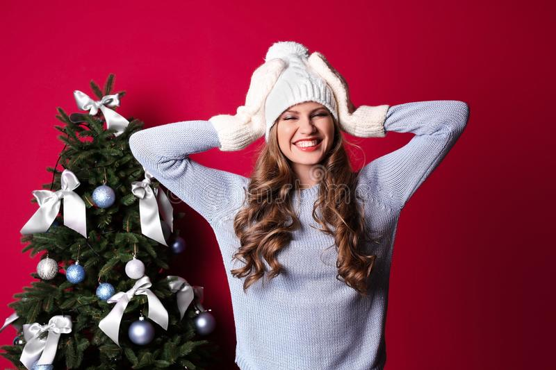 Beautiful young woman in hat and mittens near Christmas tree royalty free stock photo