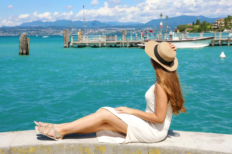 Beautiful young woman with hat sitting on wall looking at stunning landscape of Garda Lake in Sirmione, Italy stock images