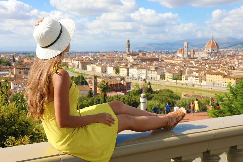Beautiful young woman with hat sitting on wall looking at stunning panoramic view of Florence in Tuscany, Italy royalty free stock photos