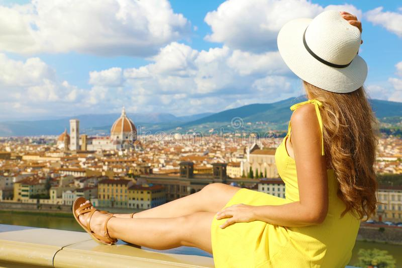 Beautiful young woman with hat sitting on wall looking at stunning panoramic view of Florence in Tuscany, Italy stock photography