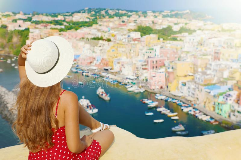 Beautiful young woman with hat sitting on wall looking at stunning panoramic view of Procida Island, Naples, Italy stock photo