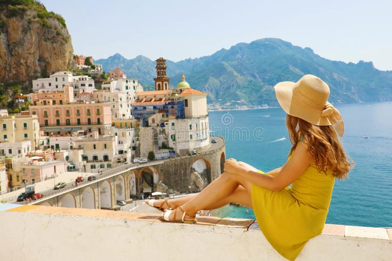 Beautiful young woman with hat sitting on wall looking at stunning panoramic village of Atrani on Amalfi Coast, Italy.  stock photo