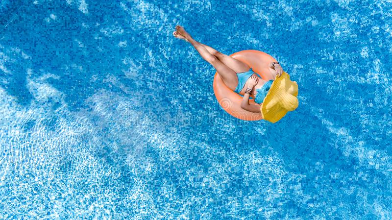 Beautiful young woman in hat in swimming pool aerial top view from above, girl in bikini relaxes and swim on inflatable ring donut royalty free stock image