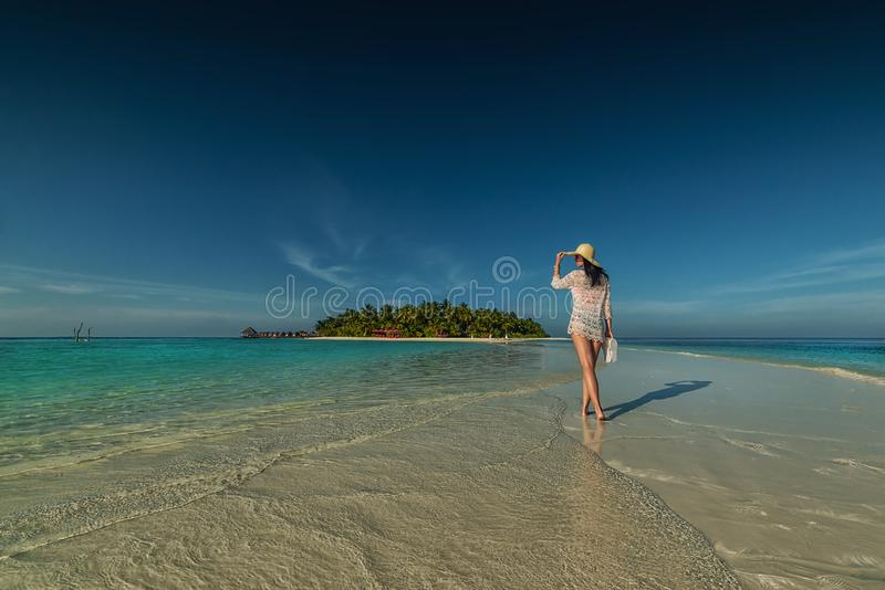 Beautiful young woman with hat on white beach, beautiful scenery with woman in maldives, tropical paradise royalty free stock photography