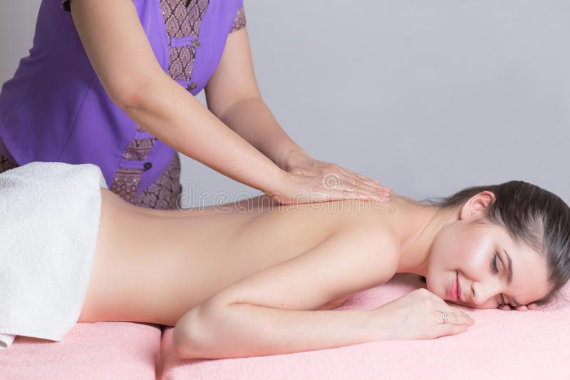 Beautiful woman having a wellness back massage and feeling visibly good about it stock images